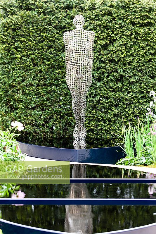 Stainless Steel sculpture in front of pool. Yew hedge behind. The Breakthrough Beast Cancer Garden. RHS Chelsea Flower Show, May 2015