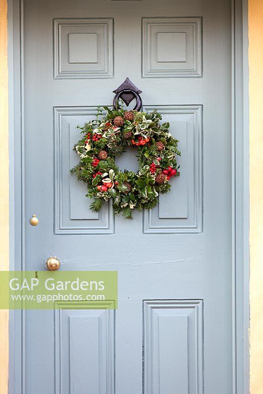 christmas wreath hanging on duck egg blue door