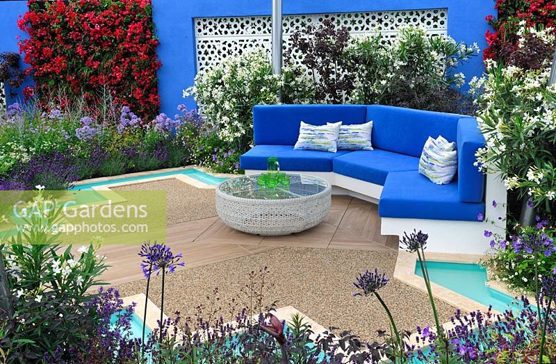 Mediterranean style garden with central pool and fountain, turquoise rills, built-in bench with blue cushions, white aluminium panels set in blue painted walls with sections of flowering bougainvillea - Noble Caledonia: Spirit of the Aegean, RHS Hampton Court Palace Flower Show 2015