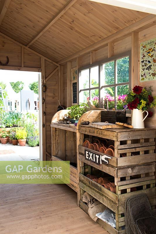 Just Retirement: A Garden For Every Retiree, view of shed interior with wooden potting bench and worktable with herbs, tools, pots and propagation equipment in a shed. Designer: Tracy Foster Sponsor: Just Retirement Ltd
