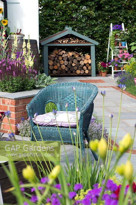 Just Retirement: A Garden For Every Retiree, view of blue painted wicker armchair and wood store. Designer: Tracy Foster Sponsor: Just Retirement Ltd