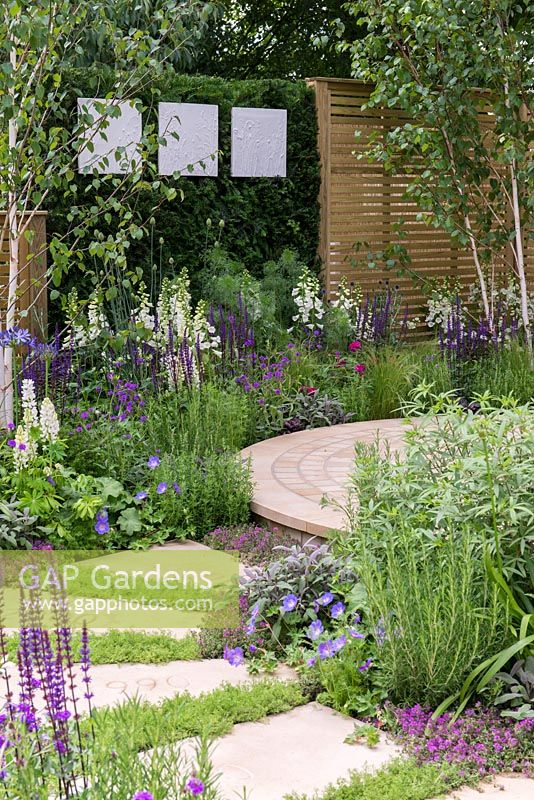 The Wellbeing of Women Garden. a circular patio is edged in medicinal and sensory plants, in purples, blues and whites. Designers: Claire Moreno, Wendy von Buren and Amy Robertson.