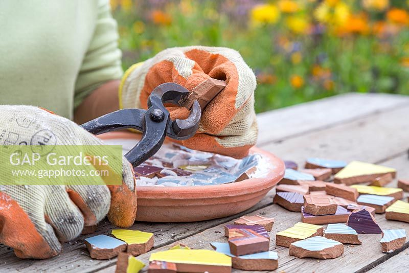 Using tile nippers to cut mosaic pieces into required shape