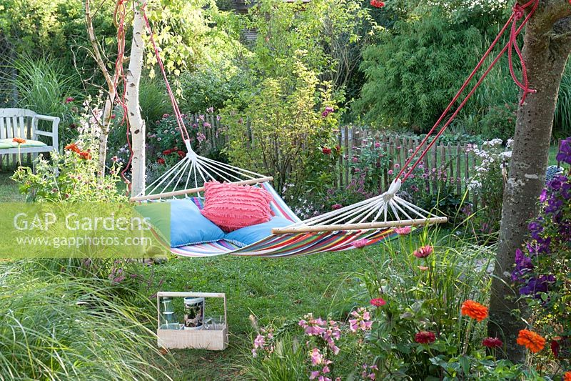 Hammock Hung Up To Relax In Small Garden Between Trees Flower Bed With Summer Flowers