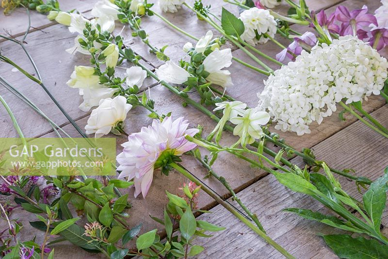 Ingredients required for constructing a White and Purple Bouquet. Plants include Scabiosa caucasica 'Fama White', Chamerion angustifolium, Lupinus polyphyllus 'Gallery White', Abelia x grandiflora, Foeniculum vulgaris, Rosa 'Tranquility', Dahlia 'Eveline', Digitalis purpurea 'Camelot White', Nicotiana affinis, Clematis viticella 'Polish Spirit', Hydrangea arborescens 'Annabelle', Dahlia 'White Aster', Jasminum officinale, Artemisia 'Powis Castle' and Cosmos bipinnatus 'Purity'