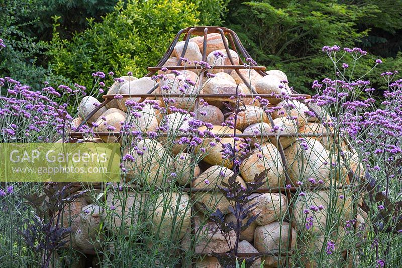 Unique Gabion sculpture shaped like a bulb, with planting of Verbena bonariensis and Actaea