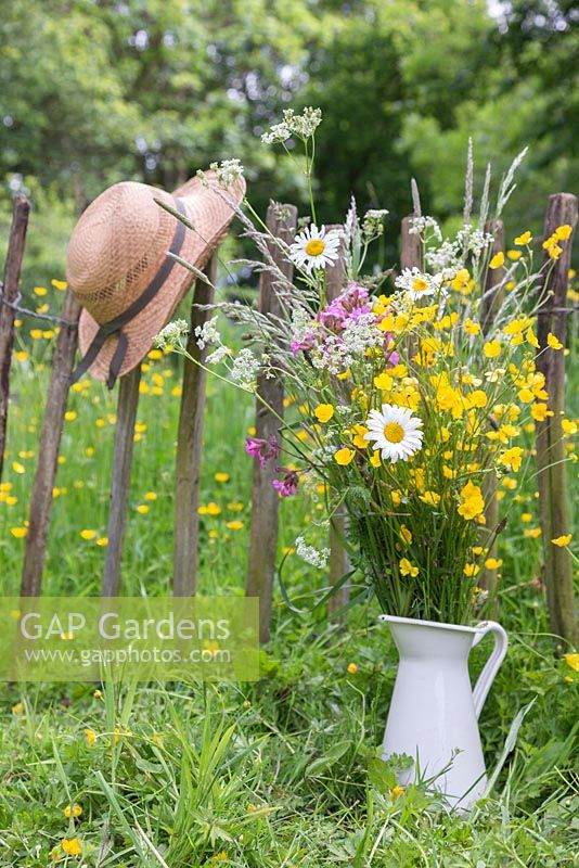 A jug of wildflowers against a rustic fence, with a view to a meadow of Buttercups - Ranunculus