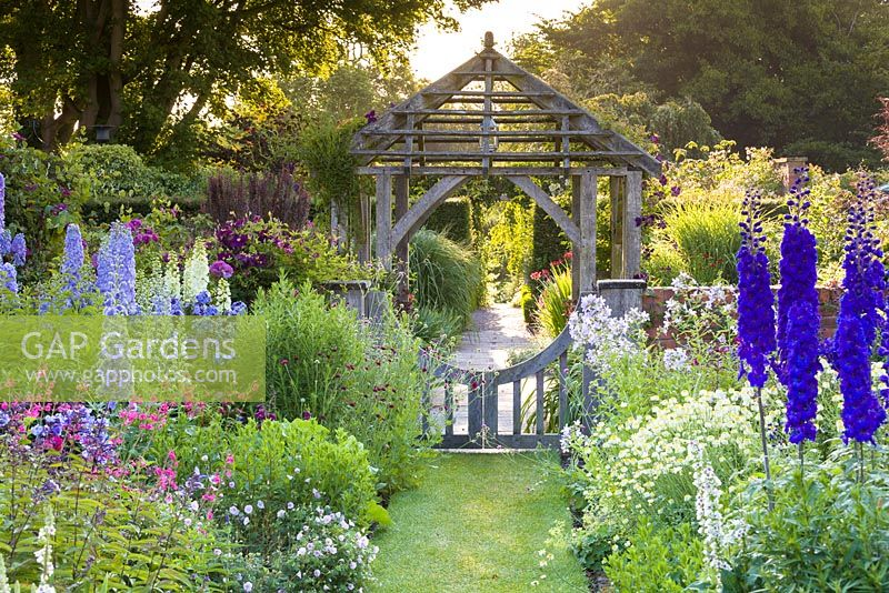 Early morning in the Sundial Garden at Wollerton Old Hall Garden, Shropshire - photographed in July. Planting includes Delphiniums, Salvia microphylla, Knautias, Verbascums, Clematis 'Warsaw Nike' and Geraniums. The oak gate was designed in Arts and Crafts style