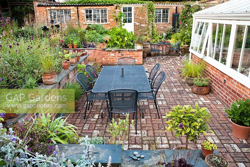 Sunken Patio Beside The Conservatory Enclosed With Brick Wall And Perennial  Borders. The Coach House