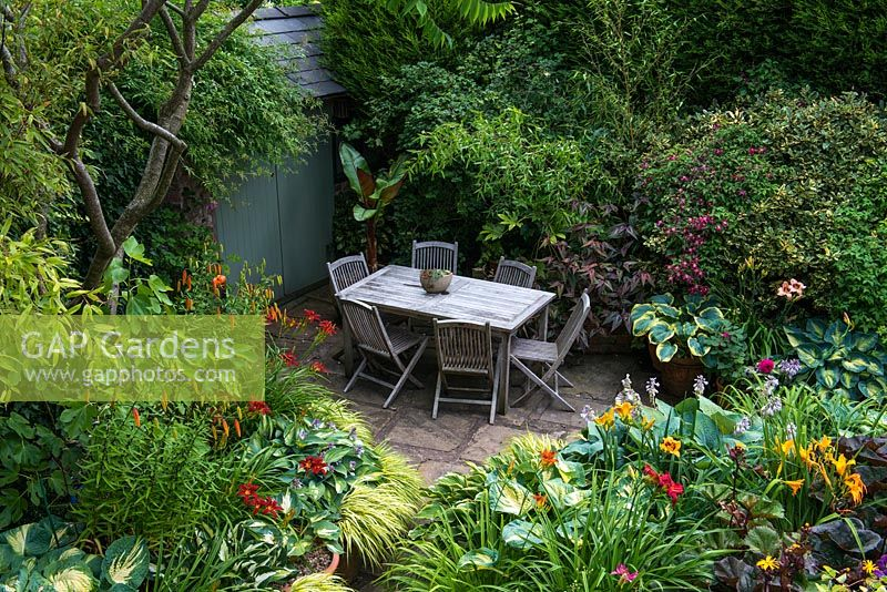 A secluded shady patio with garden furniture surrounded by lush dense borders planted with Hostas, Hakonechloa grasses, Ligularia, Persicaria microcephala, Lilium martagon, daylilies, Clematis Etoile Violette, Bamboo and a banana plant
