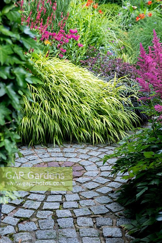 A stone set path in a circular design lined with dense herbaceous planting including yellow Hakonechloa macra Aureola grass, Persicaria Firetail, Monarda, Sedum, black Ophiopogon and Astilbe.