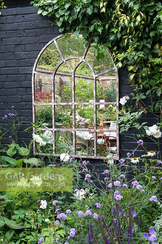 Wall mirror, edged in Cosmos 'Purity', Verbena 'Lollipop', Echinacea 'White Swan' and Rosa 'Iceberg'.