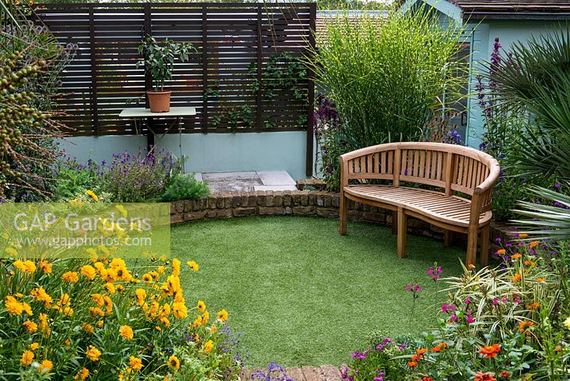 A sunken circular lawn of artificial grass, with a wooden bench in front of miscanthus sinensis 'Zebrinus'.