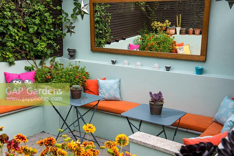 An outdoor room with built in benches between raised beds planted with Gaillardia.