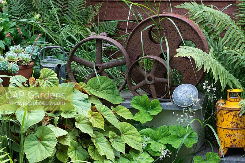 A decorative collection of metal industrial parts amongst begonia foliage and ferns.
