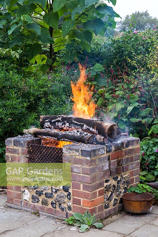 A raised brick fire pit warming the garden in late summer.