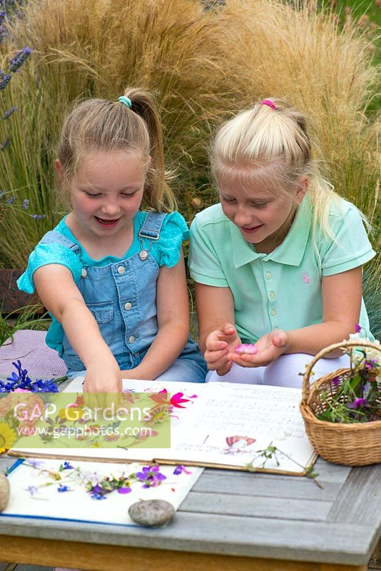 Two little girls, aged 6 and 9, pressing garden flowers in an old nursery rhyme book.