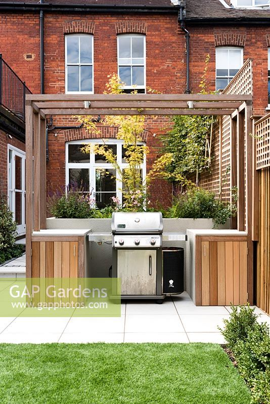 Outdoor cooking area and planting of: Salvia caradona, Buxus semperivens, Anemome japonica, Acer disectum, Astroturf, pleached hornbeam behind