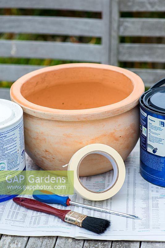 Painting a seaside themed container step by step. Step 1: You will need a porous terracotta pot, two contrasting colours of bathroom paint and masking tape.