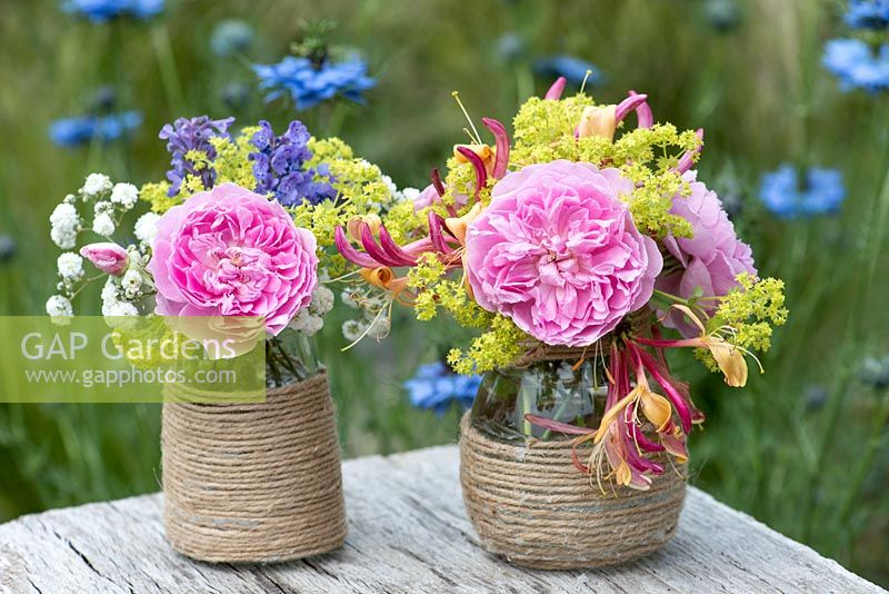 Colourful summer posies with pink rose, alchemilla, baby's breath, honeysuckle and catmint in glass jars decorated with twine.