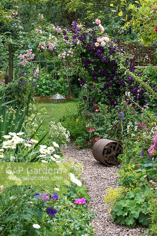 A country cottage garden with Rosa 'Belvedere', Rosa 'Compassion' and Clematis 'Etoile Violette' scrambling over a rustic arch which frames view of potager beyond. Pebble path edged in borders of leucanthemum, alchemilla, hardy geranium, fuchsia and Jacob's ladder.
