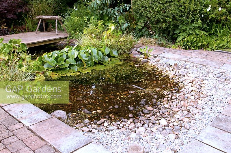 Rectangular wildllife pond adjacent to raised patio and edged with stone and brick paving and with shallow end with pebbles and cobbles