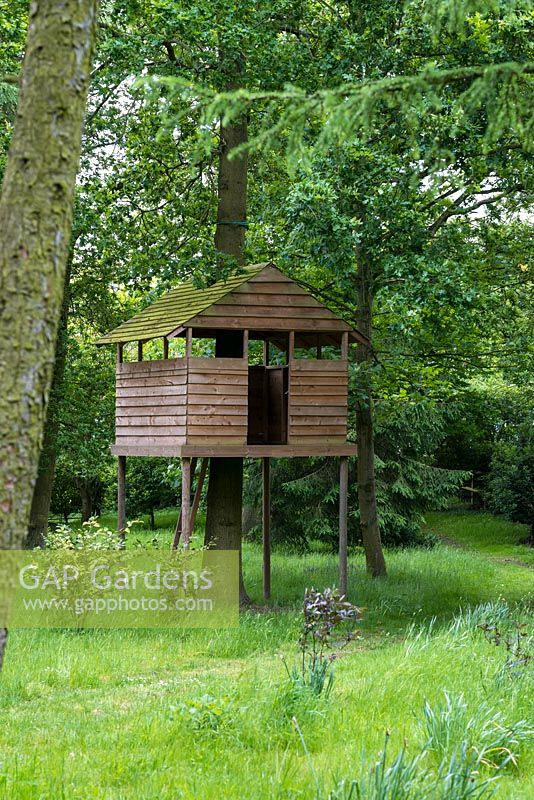 A wooden treehouse sits on stilts in woodland.