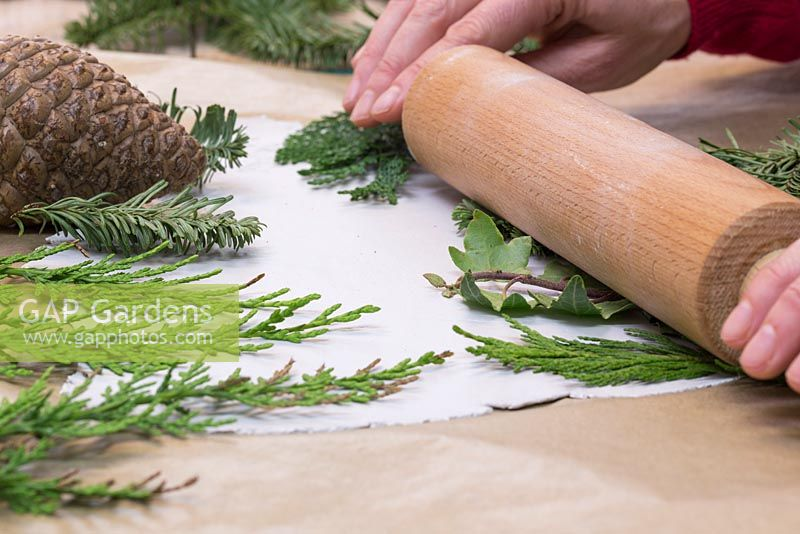 Using a rolling pin to gently apply an imprint into the clay, using a variety of foliage