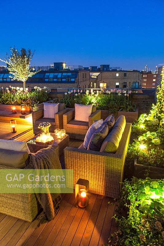 Outside seating area on a London roof terrace at night with candles and outside lighting.  April.