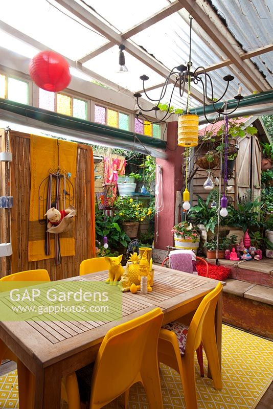 Inner city garden with begonias and spathiphyllums features colourful eclectic retro pieces sourced from local markets, including a timber dining setting with yellow chairs