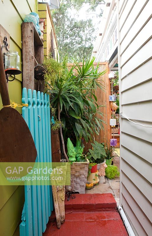 View up side passage of house to garden at back with a blue painted picket fence potted plants and a green garden Gnome statue.