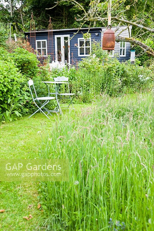 The Wild Garden where grass is allowed to grow long and bulbs are naturalised, with Debbie's studio in the corner.