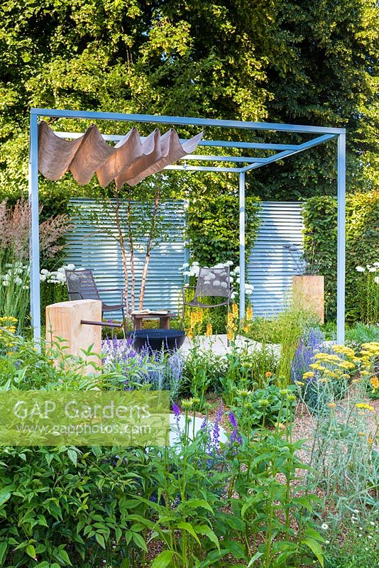 Retreat Garden, Steel Pergola With Canvas Awning Stands Over Metal Table  And Chairs On White Paved Raised Terrace Area With Gravel Surrounding.