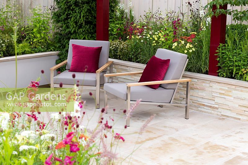 Squire's 80th Anniversary Garden, detail of a pair of grey padded stainless steel chairs with teak arms and burgundy cushions which echo the colour of the uprights of the pergola under which they sit. Yorkstone paved terrace is surrounded by walls and raised beds. Plants include Cosmos bipinnatus 'Xanthos', Achillea millefolium 'Paprika', Pennisetum orientale and Sanguisorba 'Chocolate Tip'.  RHS Hampton Court Flower Show 2016