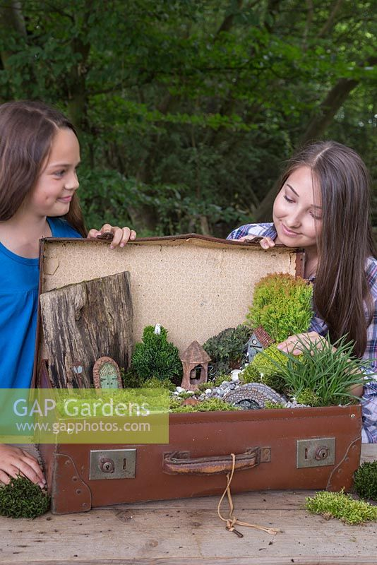 Two girls happy with their completed miniature garden project