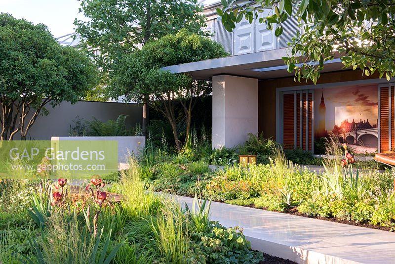limestone walkway with iris kent pride in foreground vestra wealths garden of mindful