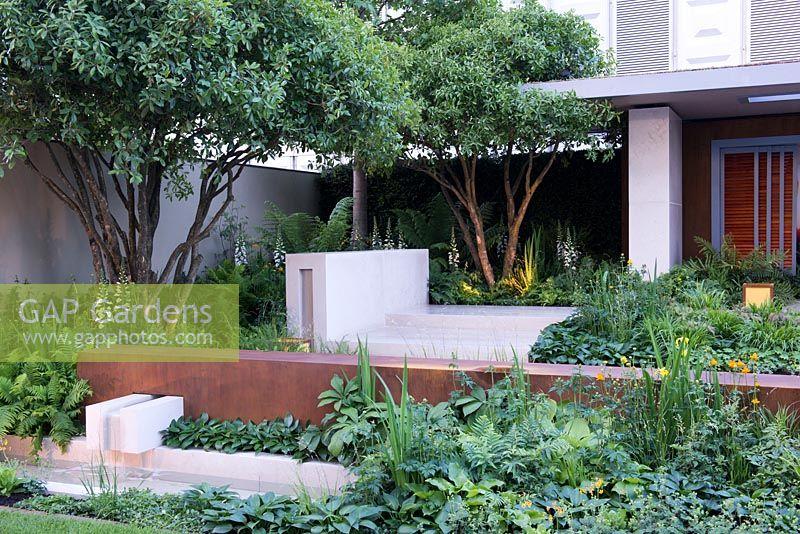 limestone and corten steel water feature green planting of hosta devon green rodgersia and ferns vestra wealths garden of mindful living