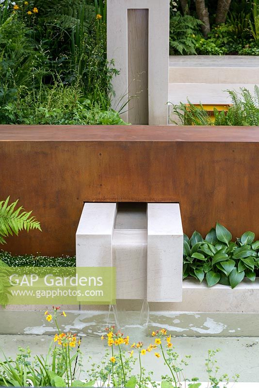 garden of mindful living with limestone rill water feature and corten steel wall planted with primula sagina senior and hosta devon green