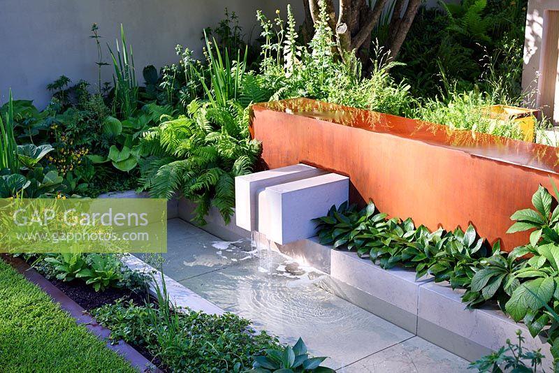 vestra wealths garden of mindful living waterfall into rill through limestone blocks in a modern
