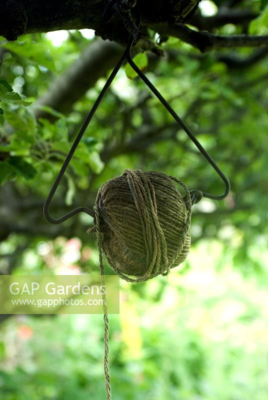 Ball of garden twine on hanger in tree