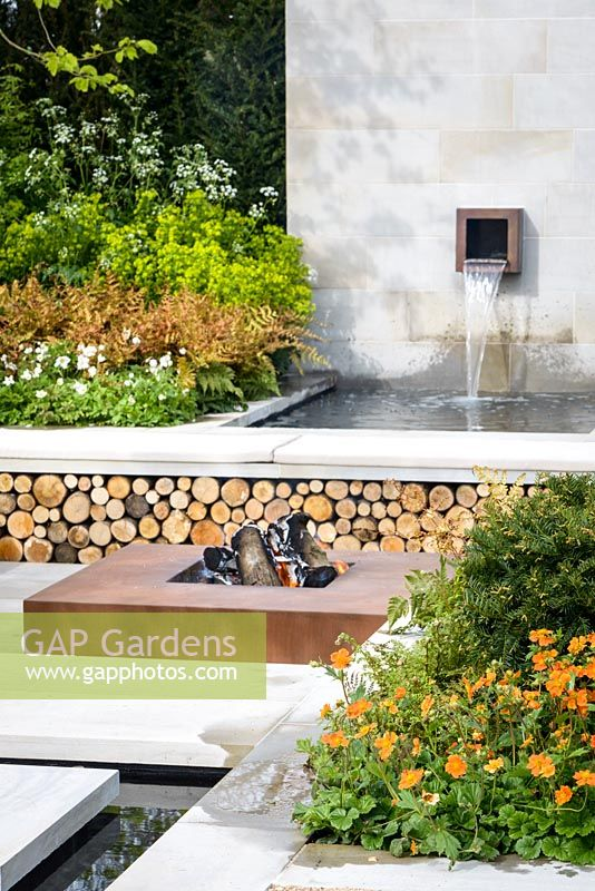 Corten Steel square fire pit, a bench with log store and feature , surrounded by Geum 'Borisii', Dryopertis erythrosora, Anemone sylvestris and Euphorbia robbiae. The Sunken Retreat Garden, RHS Malvern Spring Festival 2016. Design: Ann Walker, Graduate Gardeners