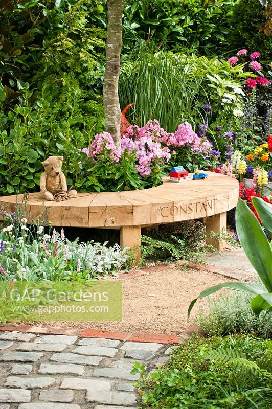 The NSPCC Legacy Garden, Hampton Court Palace Flower Show 2014. Teddy bear and children's toys on wooden bench surrounded by colourful mixed planting