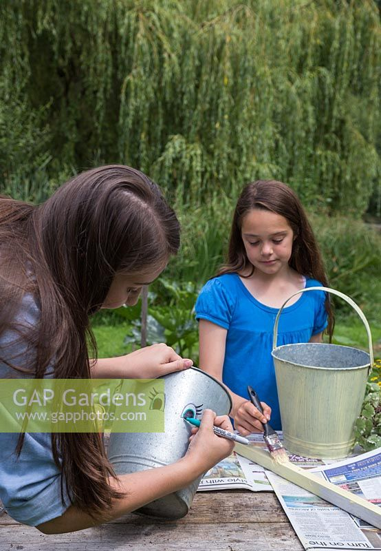 A girl drawing a face onto a galvanised bucket