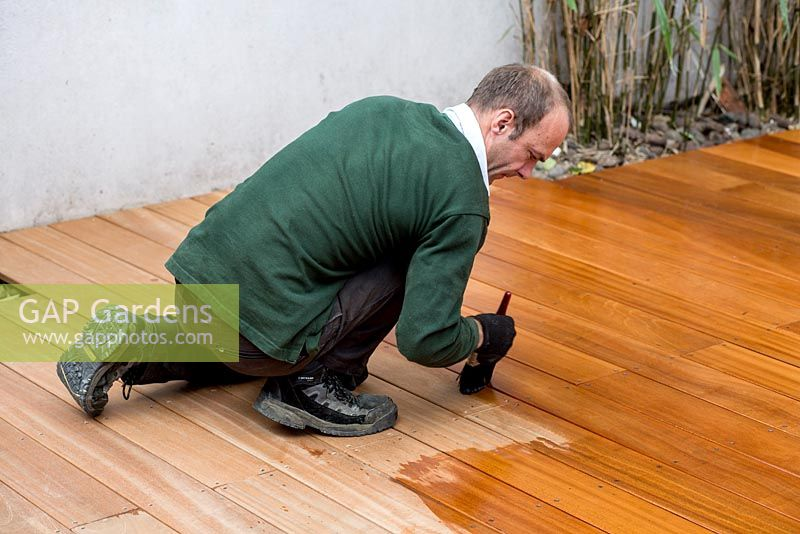 Applying wood oil to finished decking in small urban garden