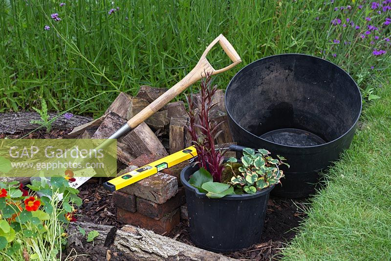 Materials required for creating a barrel pond, a plastic trug, spade, bricks, logs, spirit level and aquatic plants