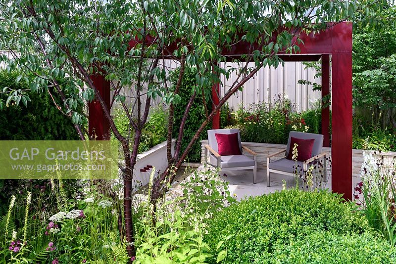 Squires 80th Anniversary Garden. Contemporary patio area, pergola and chairs. Designer: Catherine MacDonald, Sponsors: Squires Garden Centres. RHS Hampton Court Palace Flower Show 2016