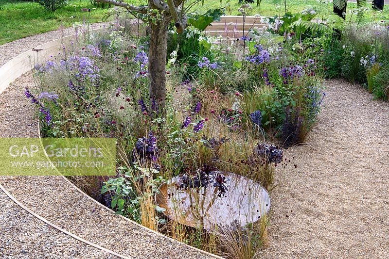 All The World's Stage. Sunken garden with semi wild woodland style planting. Shallow water basins. Gunnera, Dryopteris, Agapanthus, Thalicutrum, Verbena, carex and eryngium. Designer: Lunaria Landscapes. RHS Hampton Court Palace Flower Show 2016