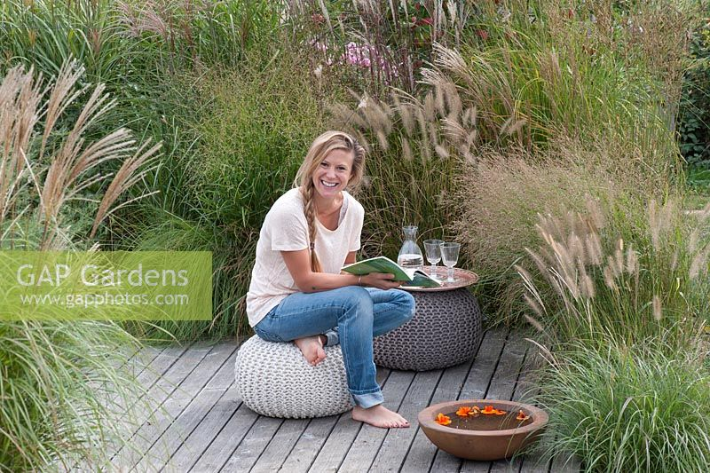 Woman relaxing on deck. Border with grasses - Pennisetum, Miscanthus and Panicum