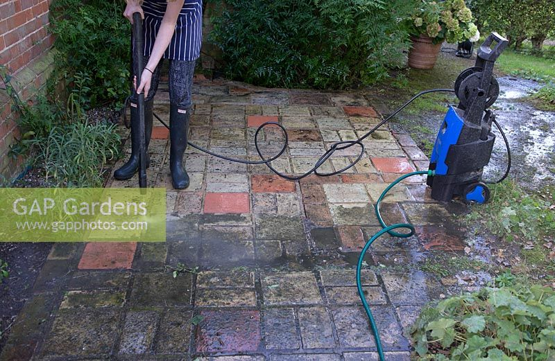 Pressure washer being used to clean a paving area in autumn