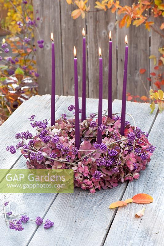 Wreath made of hydrangea flowers with branches of Callicarpa and 6 purple candles